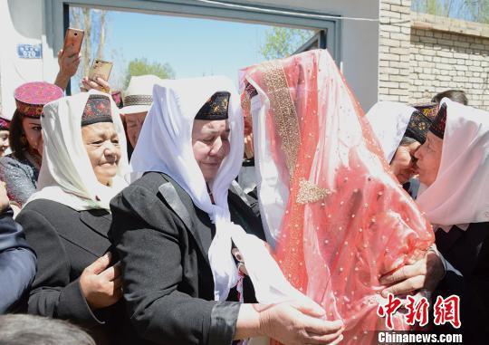 新娘祖木莱提的父母在大门口送别女儿,爸爸妈妈都留下了不舍的泪水。 勉征 摄