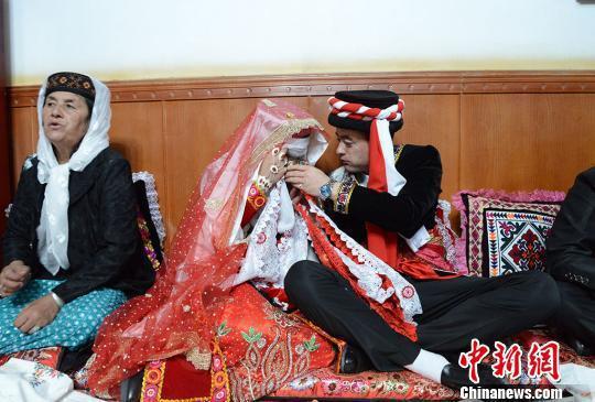 新郎卡比力正在喂自己的新娘子祖木莱提喝茶,婚礼仪式结束后,这对新人将启程前往男方家。 勉征 摄