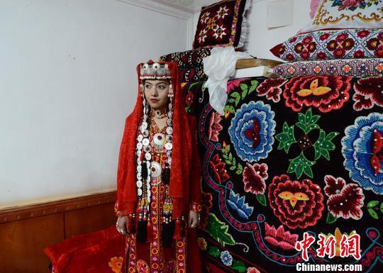 盛装打扮的新娘祖木莱提在她的闺房中等待接亲队伍的到来。屋外是庆祝婚礼载歌载舞的人群。 勉征 摄