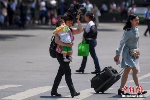 5月15日,湖南長沙持續高溫,市民頭頂烈日出行。 中新社記者 楊華峰 攝