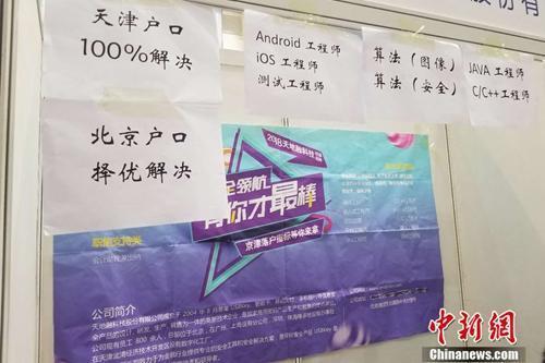 资料图:2018年4月12日,北京某高校内的毕业生双选会上,一家企业贴出了解决户口的告示。 冷昊阳 摄
