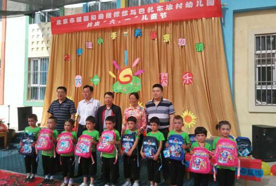 图为北京援疆干部在墨玉县托胡拉乡阿亚克古热村幼儿园与维吾尔族小朋友合影。
