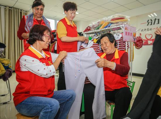 """在呼图壁县""""阿同汗""""社区的爱心超市里,王桂珍(右一)与""""阿同汗""""志愿服务队的队员们一起整理衣服。"""