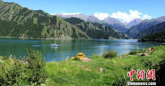 新疆天山天池风景区碧波荡漾,雪山巍峨熠熠生辉。 王小军 摄