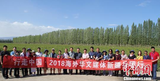 海外华文媒体一行在新疆兵团第二师二十一团辣椒地采访后留影。 戚亚平 摄