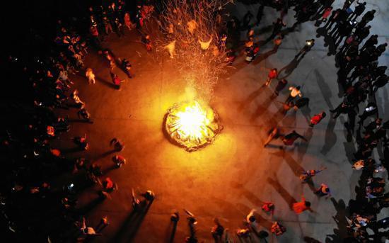 当晚,在尉犁县墩阔坦乡霍尔加村小广场,游客和村民们围着篝火跳起热情的舞蹈。  李飞  摄