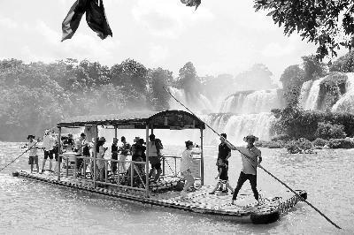 图:游客在中越边境的归春河上观赏瀑布(郭凯倩)