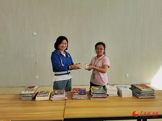 圖為北京援疆老師劉愛華(左)為幼兒園捐書。