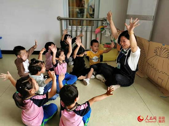 圖為北京援疆教師劉愛華為幼兒示范動作。