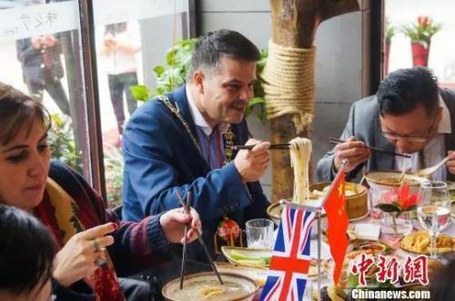 资料图:2016年1月13日,英国市长访华代表团在柳州市品尝螺蛳粉。 黄威铭 摄