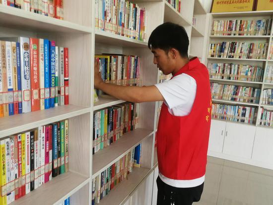 张强正在整理图书馆图书(图片均宁夏日报记者 张晓芳摄)
