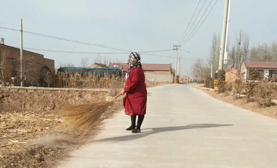 保洁员马文霞在打扫村道