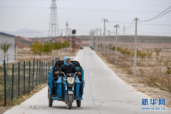 李耀梅骑着电动三轮车从家里出发去工厂(10月27日摄)。新华社记者 冯开华 摄