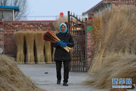 李耀梅在搬运做好的高粱笤帚(1月14日摄)。新华社记者 冯开华 摄