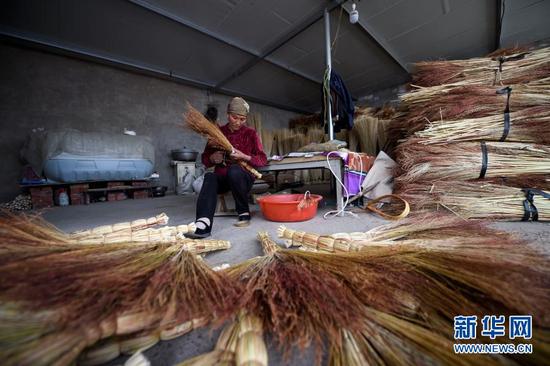 李耀梅在自家院子里建起了简易的扫帚车间。这是她在扎笤帚(2019年4月28日摄)。新华社记者 冯开华 摄