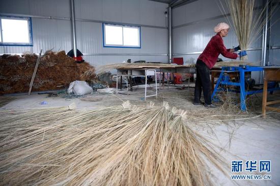 李耀梅在扶贫工厂用自己制作的机器扎制扫帚(10月26日摄)。新华社记者 杨植森 摄