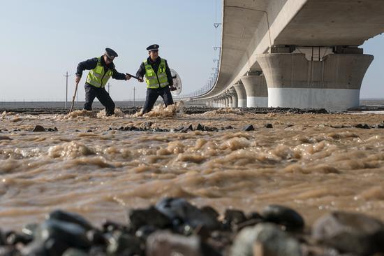 中午,雪水化了,形成了没过小腿的湍流小河,吐鲁番北站派出所园艺场警务区民警涉水巡查线路。