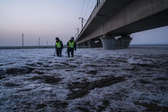 吐鲁番早晚温差大,清晨和傍晚,吐鲁番北站派出所园艺场警务区民警踏冰巡查高铁线路。