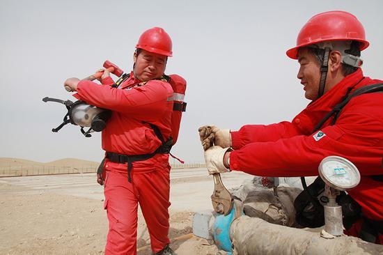 顺北油气管理部运行班在紧固SHB1-10H井管线卡箍螺丝。
