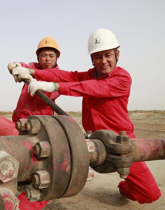 3月5日,采油二厂采油管理一区技能大师吴登亮带领员工连接井口管线。