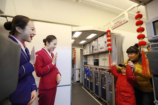2月16日凌晨,南航CZ8520航班乘务长熊元梓和乘务员赵珍与小乘客挥手告别。张思维摄