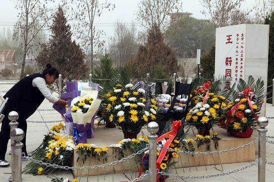 """新疆司法厅驻和田县尤库日巴格其村""""访惠聚""""工作队队员向王蔚墓敬献鲜花。"""