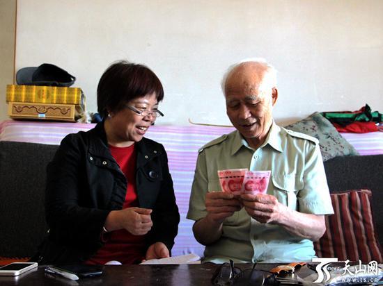 """乌鲁木齐市水磨沟区新民东街3号85岁的老人王爱钦(右一),领到""""幸福工程""""高龄老人津贴。"""