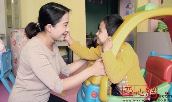 """阿依努尔在""""母亲之家""""和脑瘫患儿在一起。通讯员 王振强摄"""