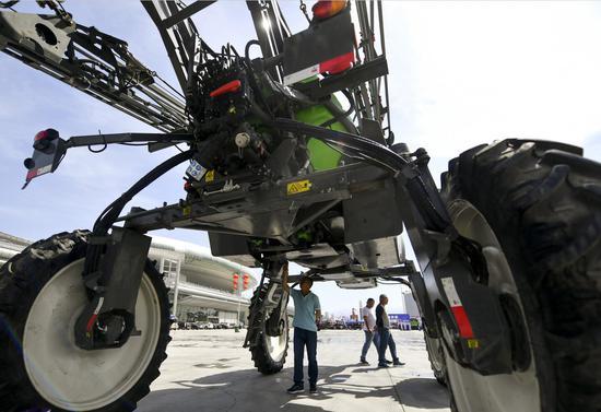 """5月5日-7日,2018新疆农业机械博览会在位于乌鲁木齐市红光山的新疆国际会展中心开幕。据介绍,本届展会以""""特色创新?精准高效""""为主题,来自德国、意大利、加拿大、法国等国家的国际品牌及中国知名企业,共计300余家农机企业到场展示其最新产品,吸引众多农产品生产、加工企业及农业种植户到场选购。中新社记者 刘新 摄"""