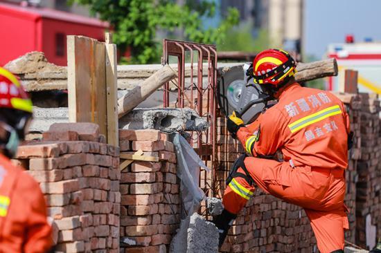 2018年5月12日,在新疆呼图壁县防震减灾应急演练活动现场,消防官兵正在震后坍塌房屋外开展切割救援工作。(陶维明 摄)