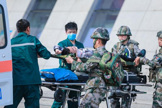 2018年5月12日,在新疆呼图壁县防震减灾应急演练活动现场,应急医疗救援队将伤员送上救护车。(陶维明 摄)