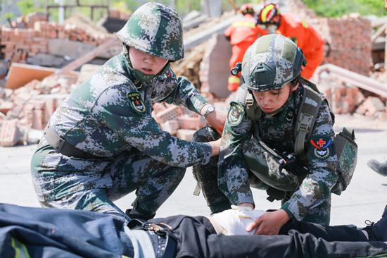 2018年5月12日,在新疆呼图壁县防震减灾应急演练活动现场,救援人员正在对伤者进行包扎。(陶维明 摄)