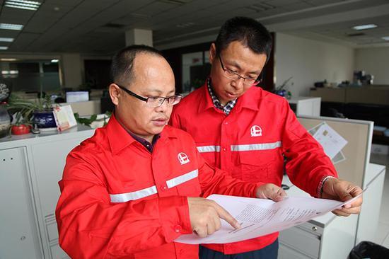 图为刘文胜(左)在给同事讲解自主研发的专利装置。