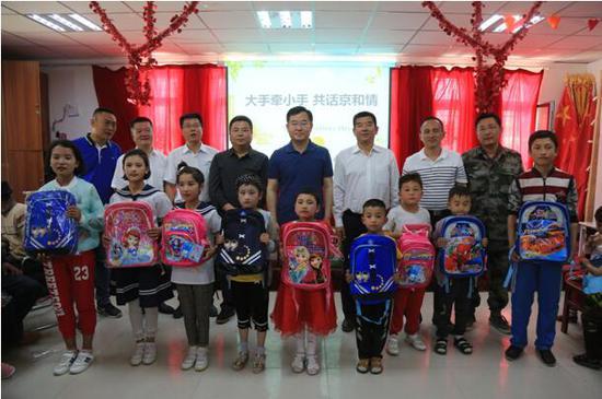 图为北京援疆干部在昆仑山深处的兵团十四师一牧场三连向连队职工孩子发放书包。