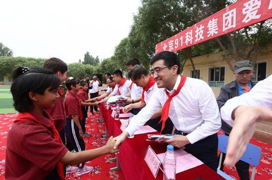 新疆墨玉县儿童福利学校的学生们为北京爱心企业家系上红领巾。 许珠珠 摄