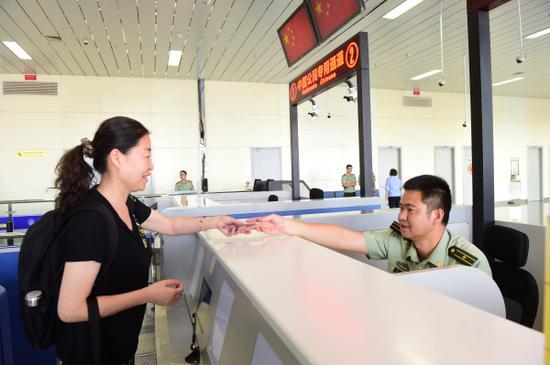 图为一名中国旅客拿好证件准备出境。李康强摄