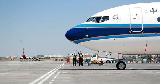 """7月进入旺季以来,乌鲁木齐机场航班量暴增,高峰时段常会""""塞车"""",机务需要在烈日下一直等待航班滑出。张思维摄"""