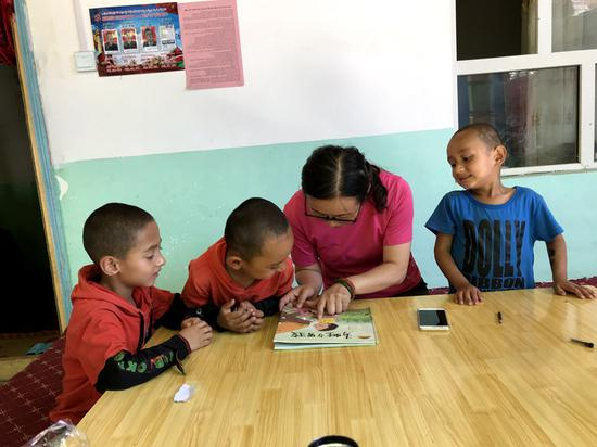 自治区测绘地理信息局工作人员指导亲戚家儿童绘画。