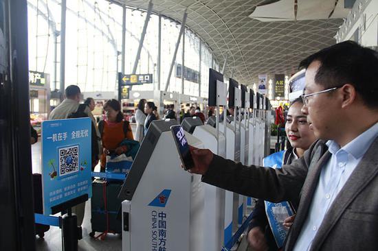 国庆期间,南航新疆分公司地面工作人员推荐旅客扫码出行。