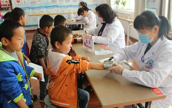 博湖县疾病预防控制中心走进该县第三小学为718名学生进行免费体检。杨建军 摄