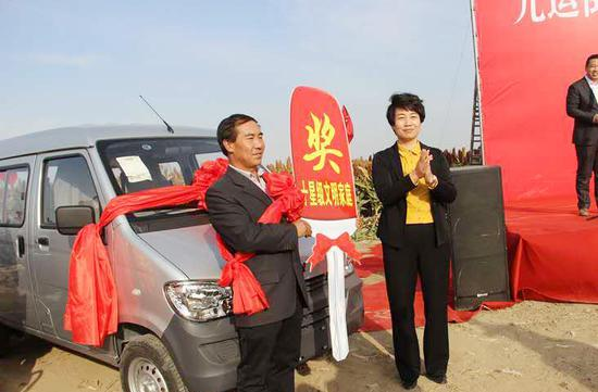 阜康市委常委、宣传部长王海燕给获奖家庭颁发奖牌。