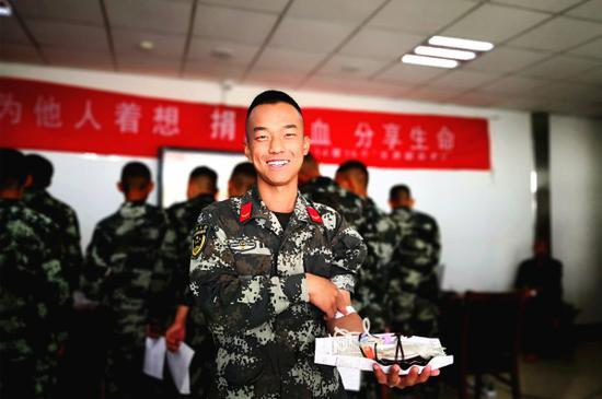 10月15日,上等兵王阿涛献血后向笔者展示储血袋。毛松  摄