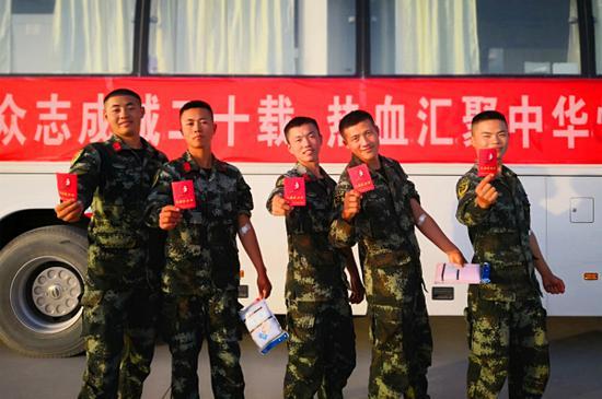 10月15日,武警兵团总队某支队七中队官兵开展无偿献血,官兵们高兴地展示自己的献血证。毛松  摄