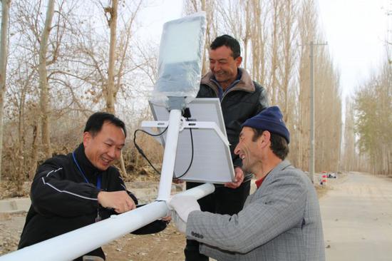 工作队副队长郑向兵和村民一起安装路灯。