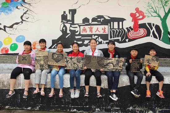 在版画之乡西畈,留守儿童们在描绘版画时学习要一丝不苟、黑白分明的人生道理  遂昌宣传部提供
