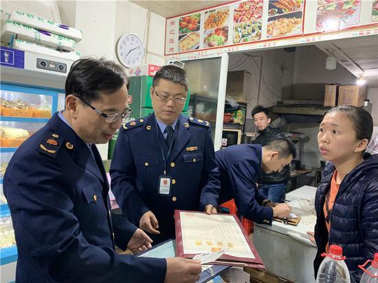 图为执法人员检查核对营业执照 鄞州区市场监管局供图