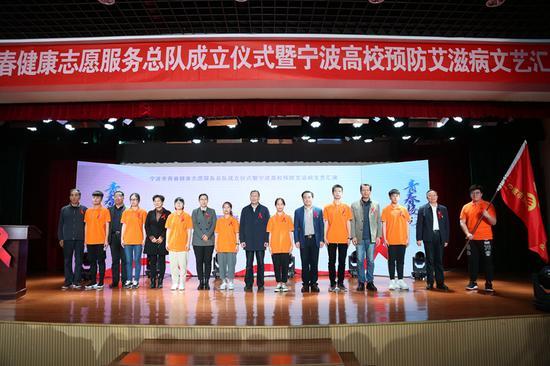 相关领导给志愿者代表佩戴红丝带。学校提供