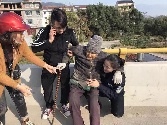 """图为:一女警察跪地用身体为老太太支起""""暖椅""""  台州公安供图"""