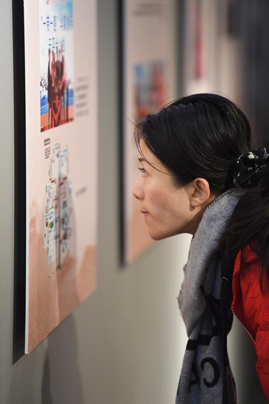 图为:一位市民在观看展出的照片。 王刚 摄