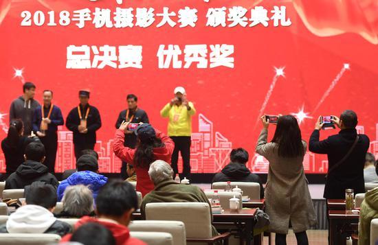 图为:与会者在用手机拍摄颁奖仪式。 张茵 摄